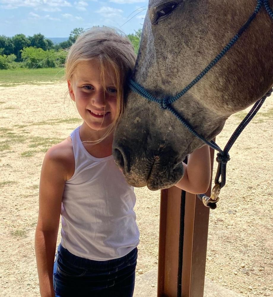 A girl smiles beside a horse at Blue Moon Ranch in Fredericksburg, TX
