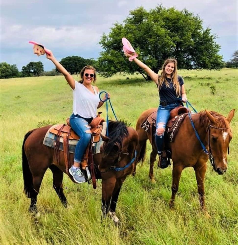 Horseback riders wave their cowboy hats at Tres Molinas Ranch & Resort in Fredericksburg, TX