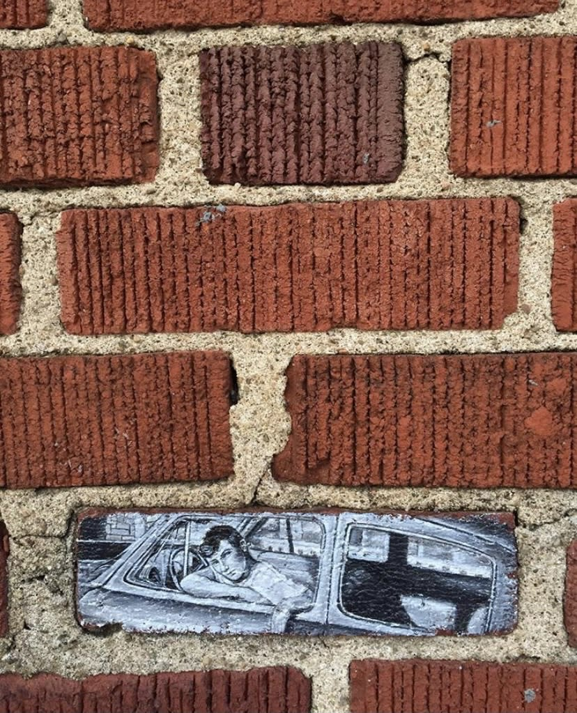 Brick painting of a man in a car by Mandi Caskey