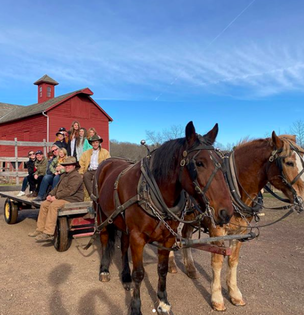 People on a horse-drawn hay ride at Howell Living History Farm