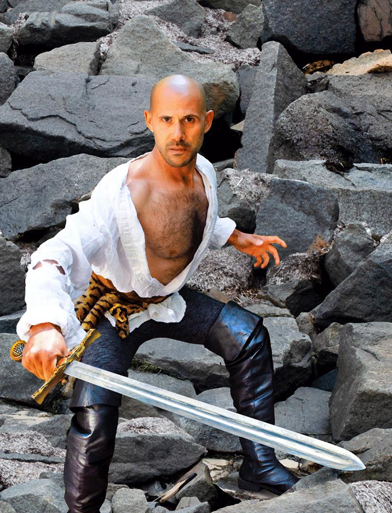 Man standing on rocks holding a sword.