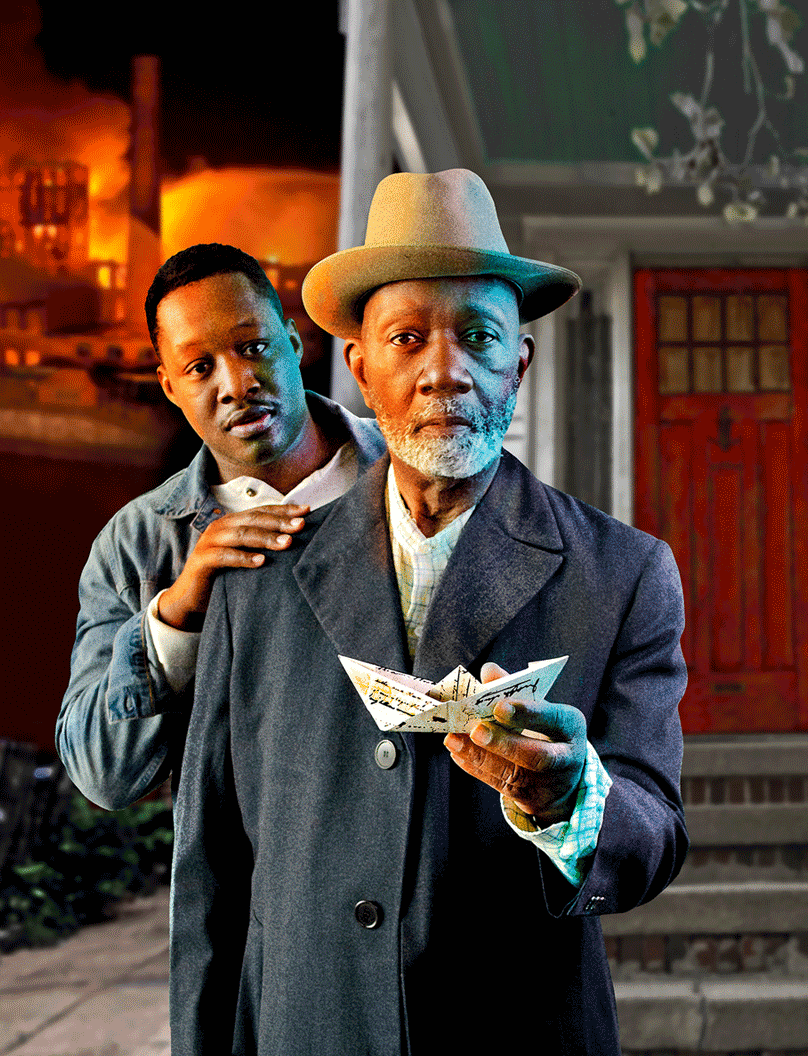 A young African American man stands behind an older African American man holding out a paper boat.