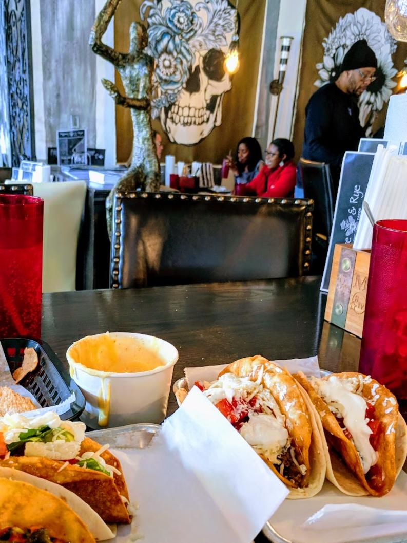 A table full of tacos, queso, red glasses, with funky art on the walls in the background at Agave and Rye in Covington, Ky.