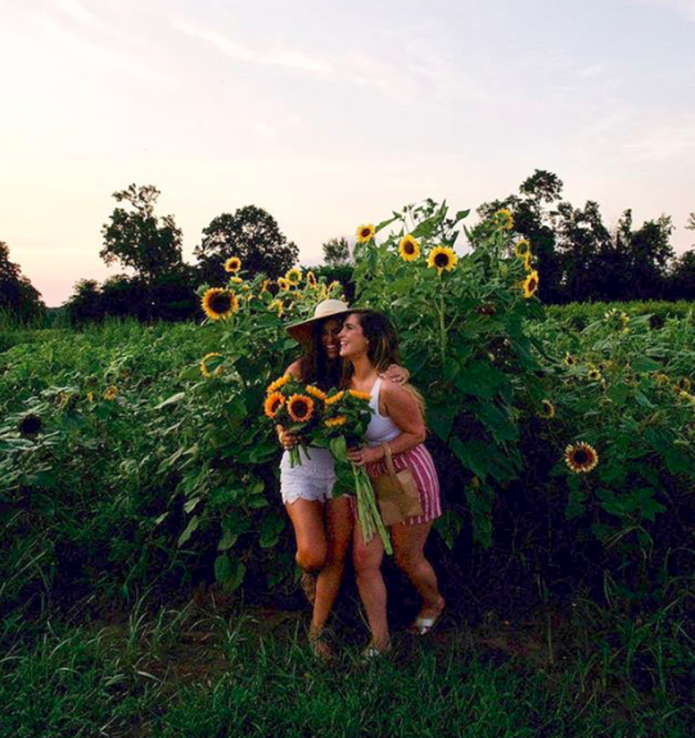 Two women holding sunflowers at Johnsons Locust Hall farm