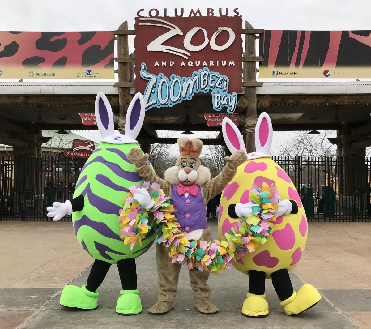 Eggs, Paws and Claws characters - two eggs and the Easter bunny - pose in front of Columbus Zoo entrance