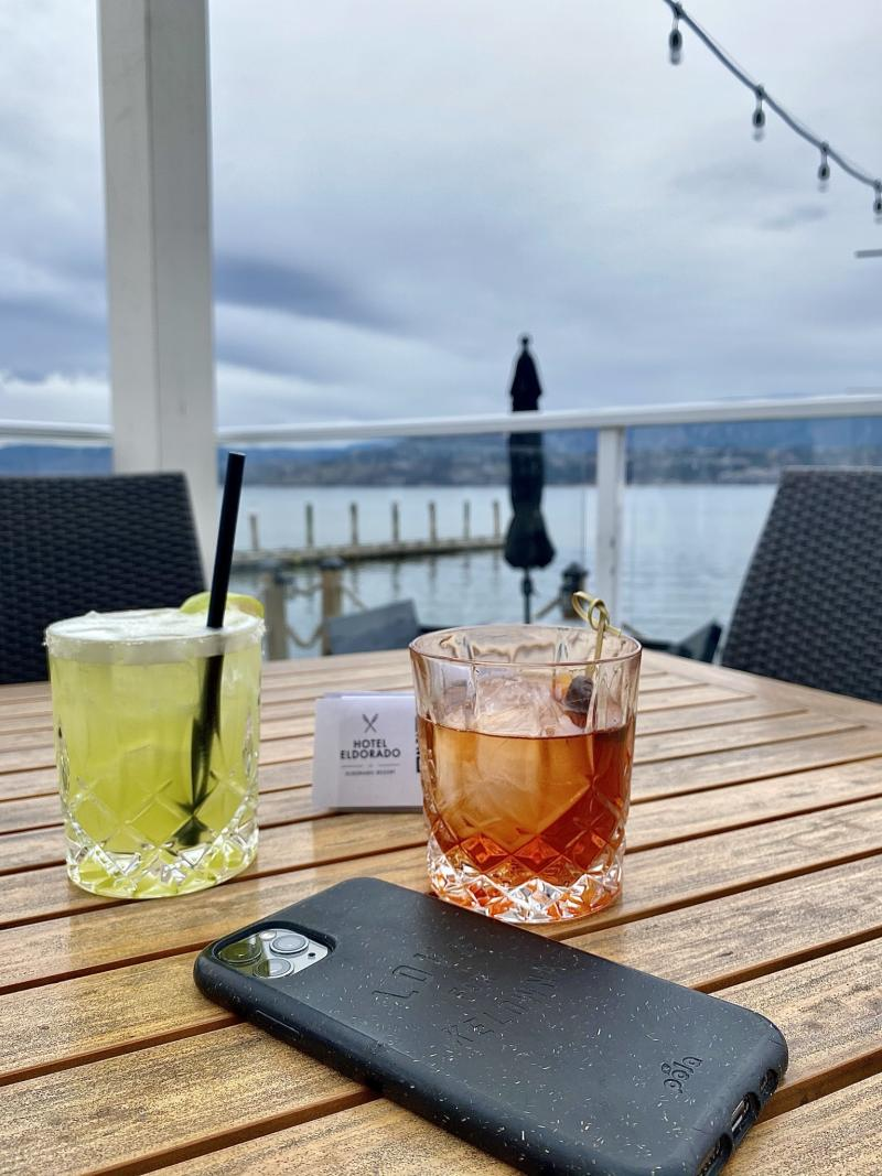 Two mixed drinks and a cell phone sit on an outdoor table overlooking the water at the Lakeside Restaurant at Hotel Eldorado