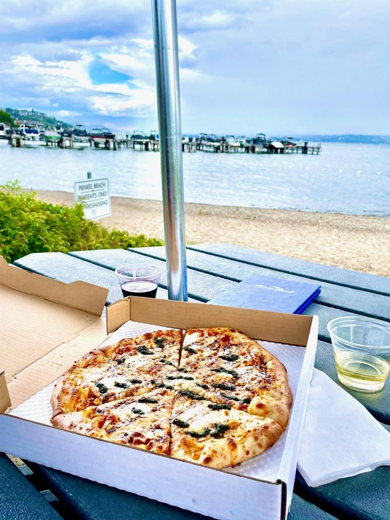 A whole pizza sitting in an open box on an outside table next to the water at Frind Winery