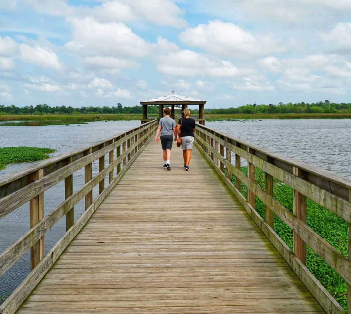 oPeople Walking Down The Pier Of Cattail Marsh In Beaumont, TX