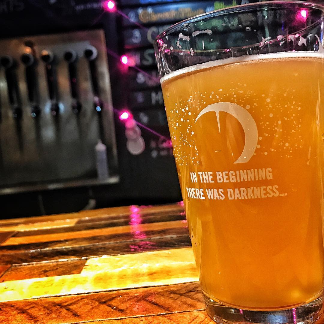 """glass of beer reading """"in the beginning there was darkness"""" with a moon graphic at darkness brewing in bellevue ky"""