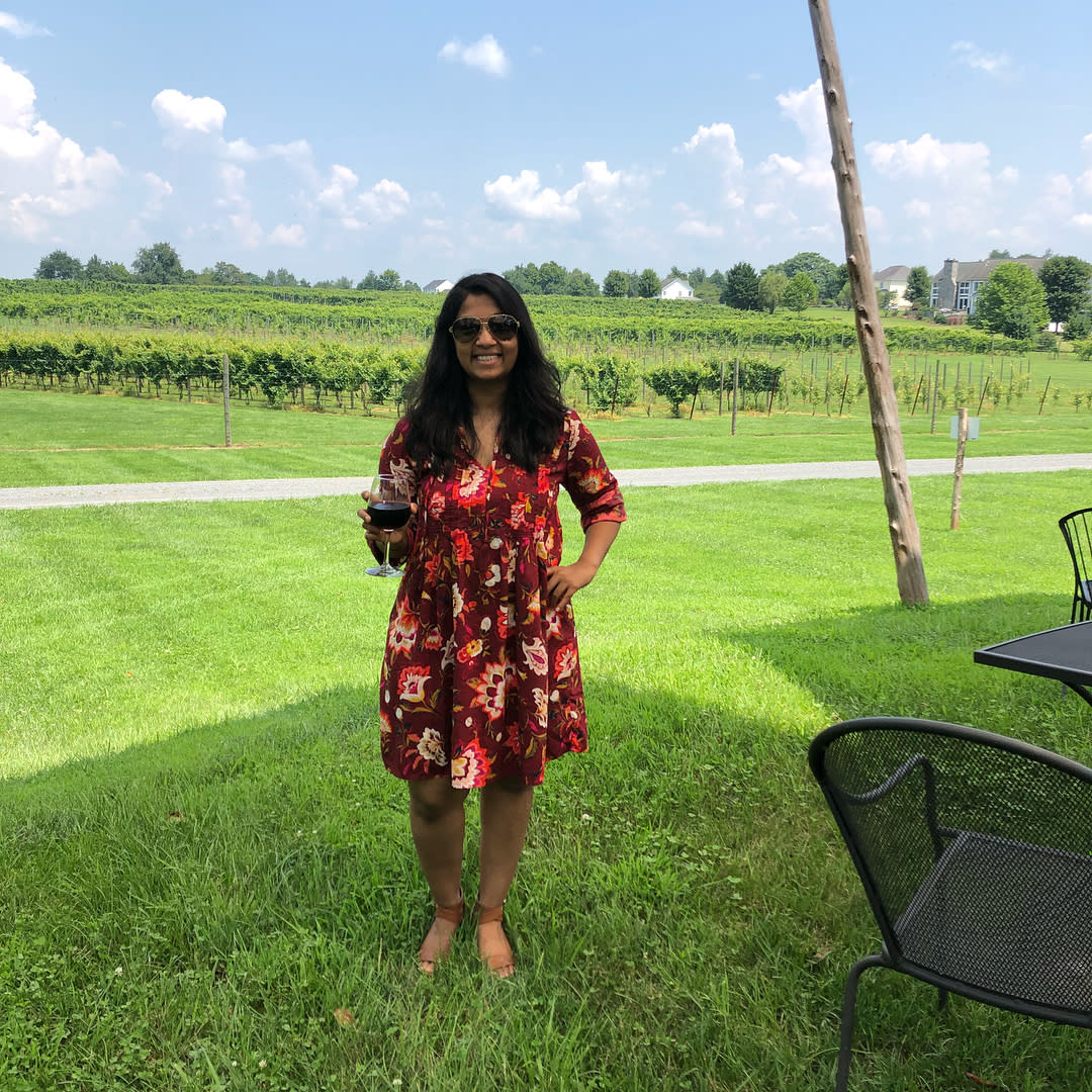 A young woman wearing a flowered dress stands outside in front of rows of vines at Fabbioli Cellars in Lucketts, VA