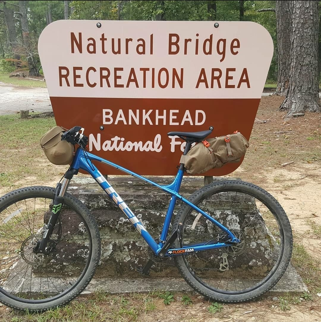 Mountain bike in front of sign for Natural Bridge Recreation Area