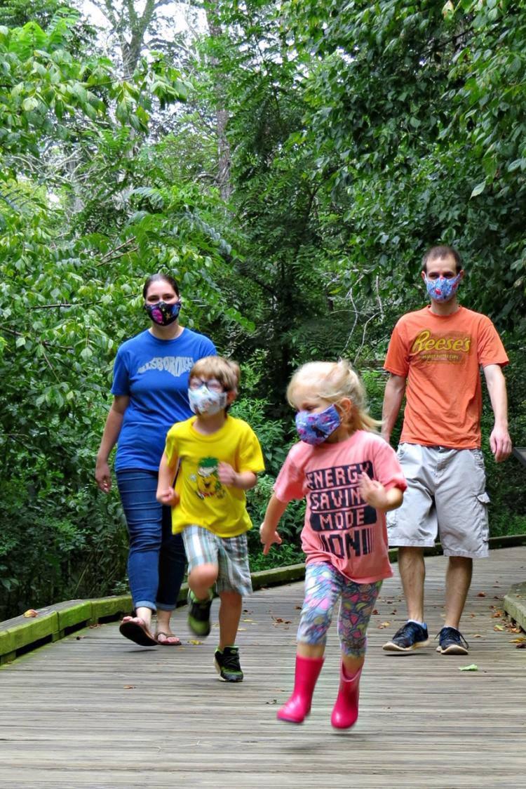Family walking along Riverwalk, wearing masks under COVID19 mandates
