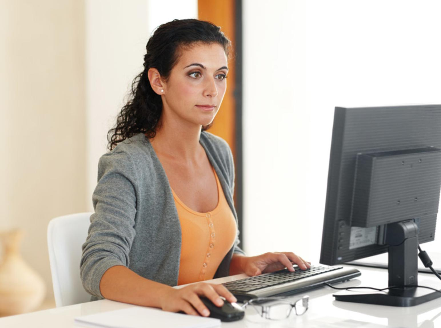 Woman sitting a desk working on a computer
