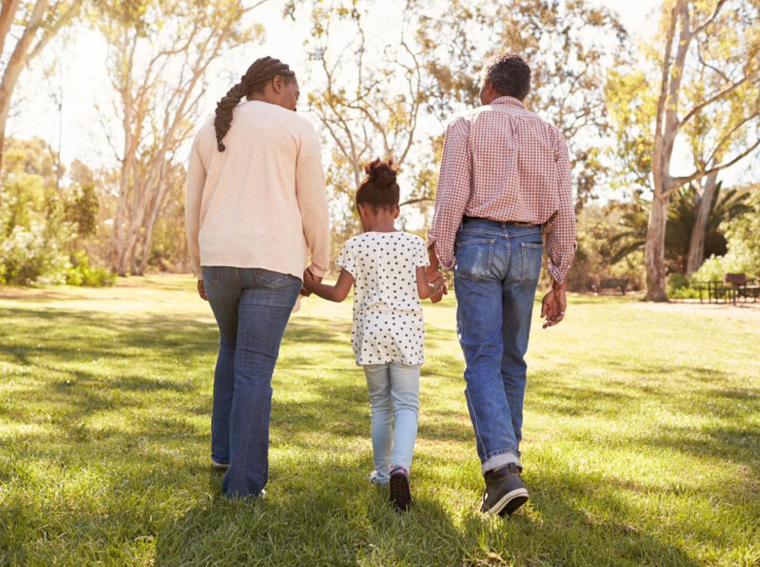 Family holding hands while walking in the park