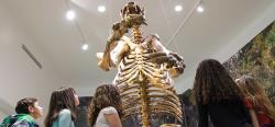 The skeleton of a giant ground sloth discovered in Daytona Beach towers over children who are looking up at it.