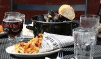 Mussel bowl, french fries, and beer on outdoor table at Cock & Bowl