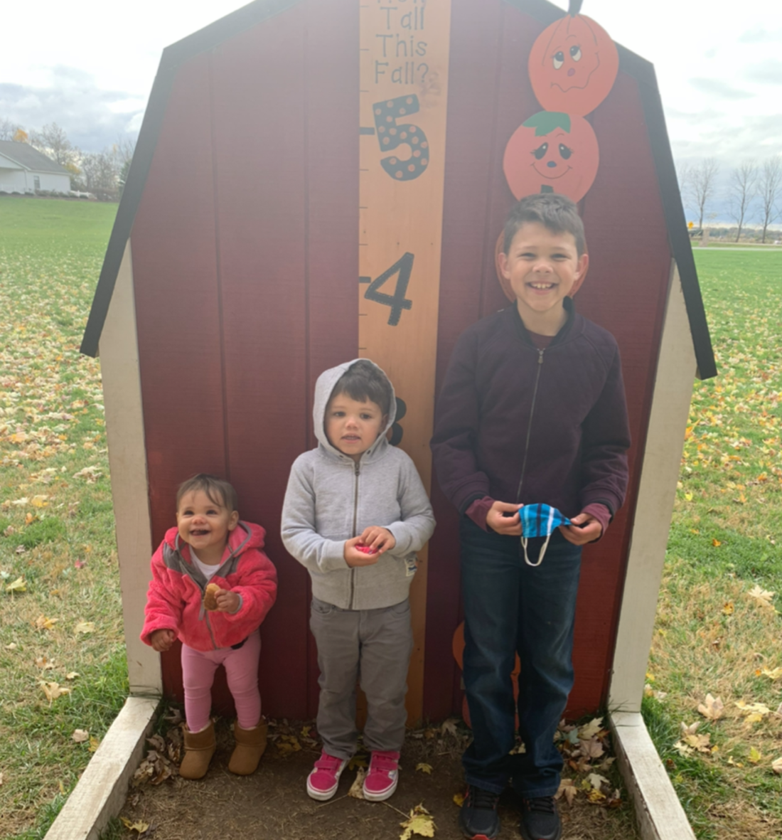 """Three kids in front of """"how tall this fall"""" measurement at a pumpkin patch"""