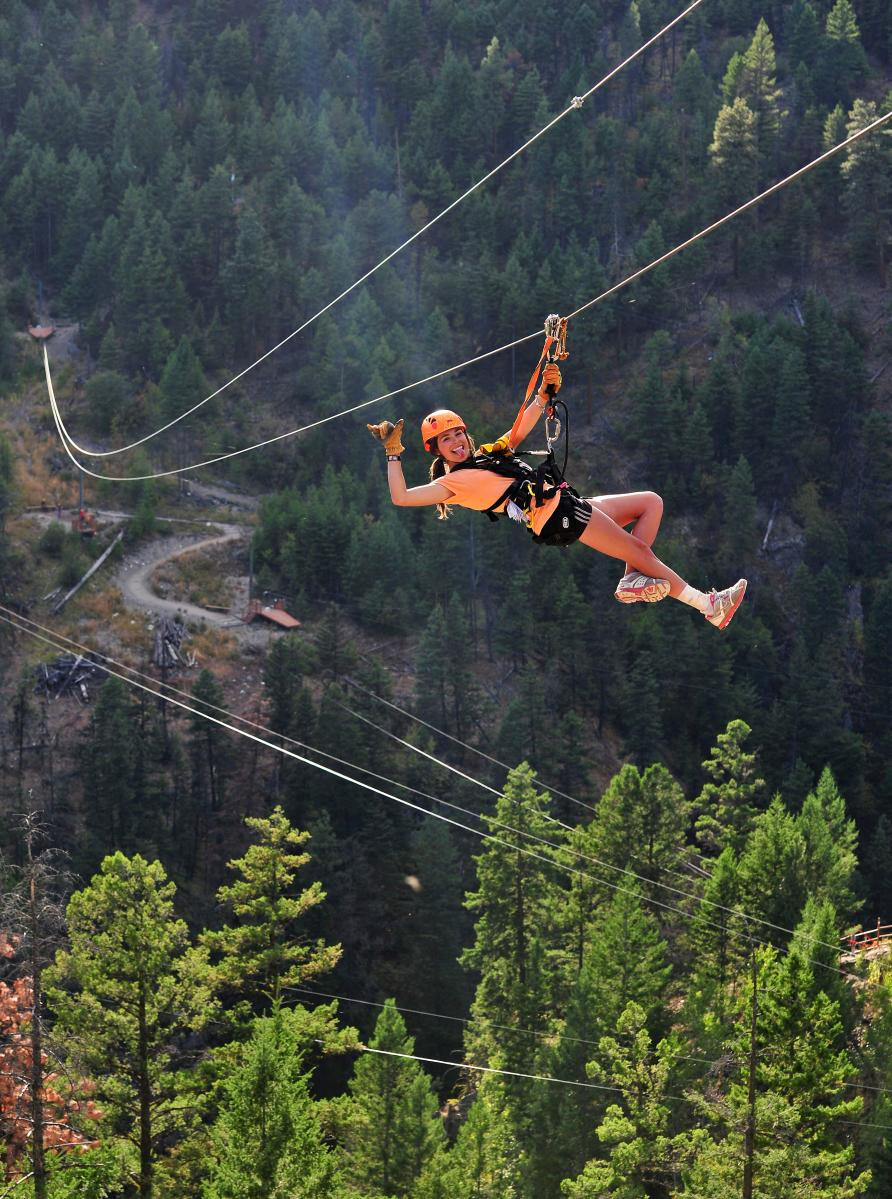 A woman rides a zipline at ZipZone Adventure Park in Peachland, BC