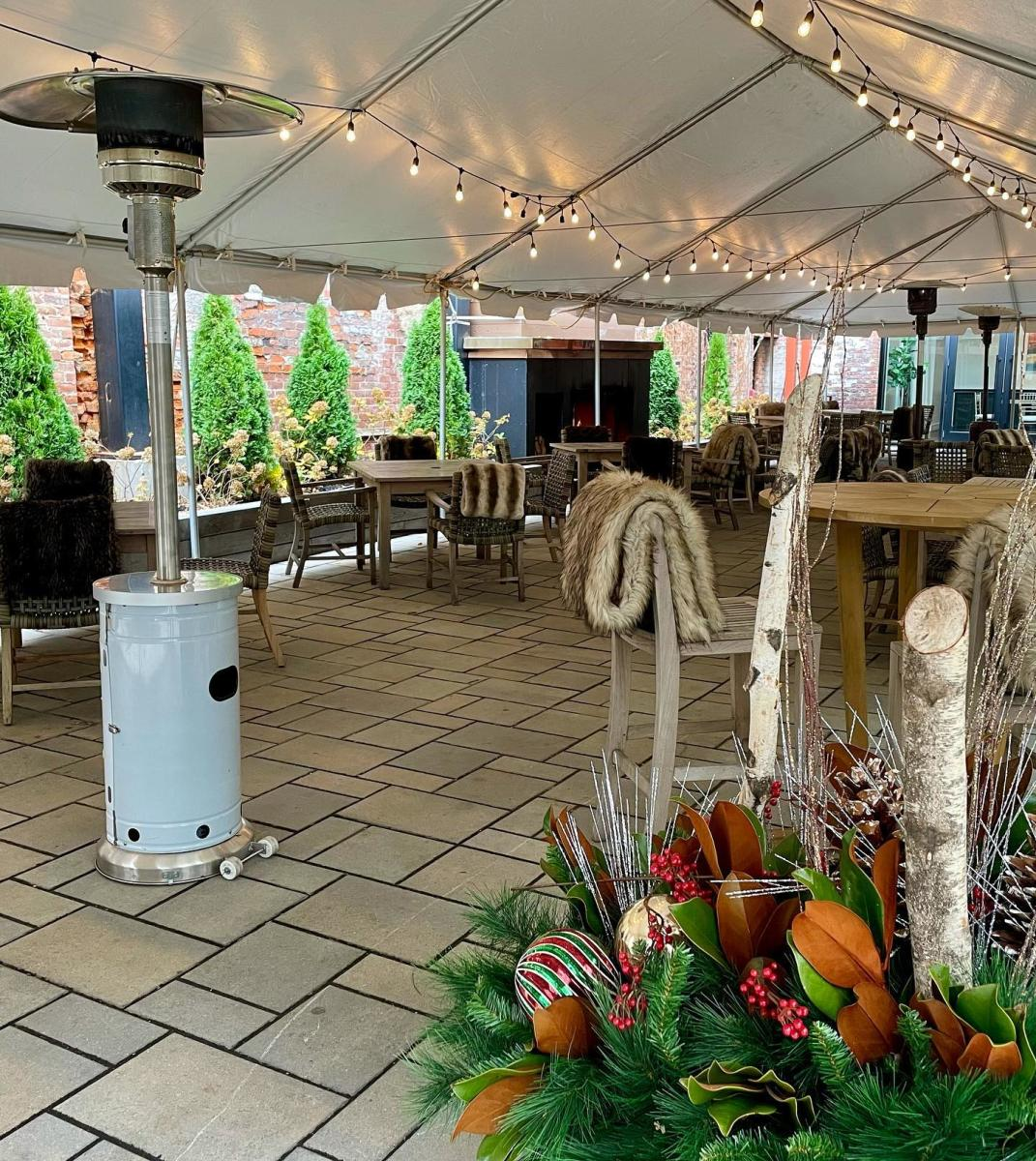 Tented patio with string lights, gas heaters, and faux furs at the tables of Coppin's restaurant