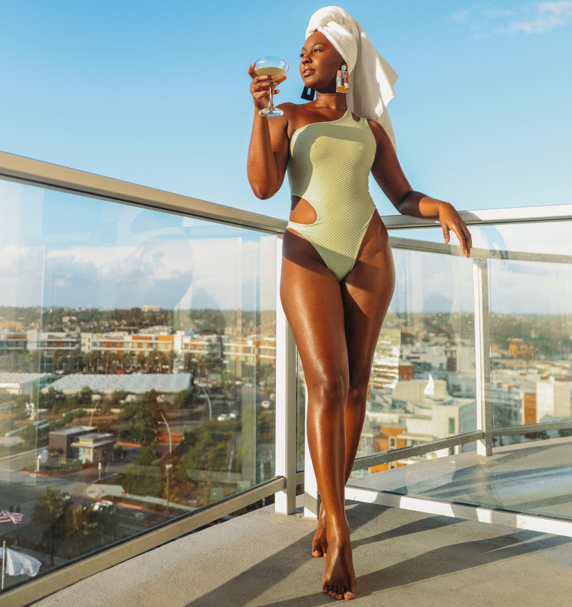 Swimsuit-clad woman enjoying a drink on a balcony at the Pasea Hotel & Spa in Huntington Beach