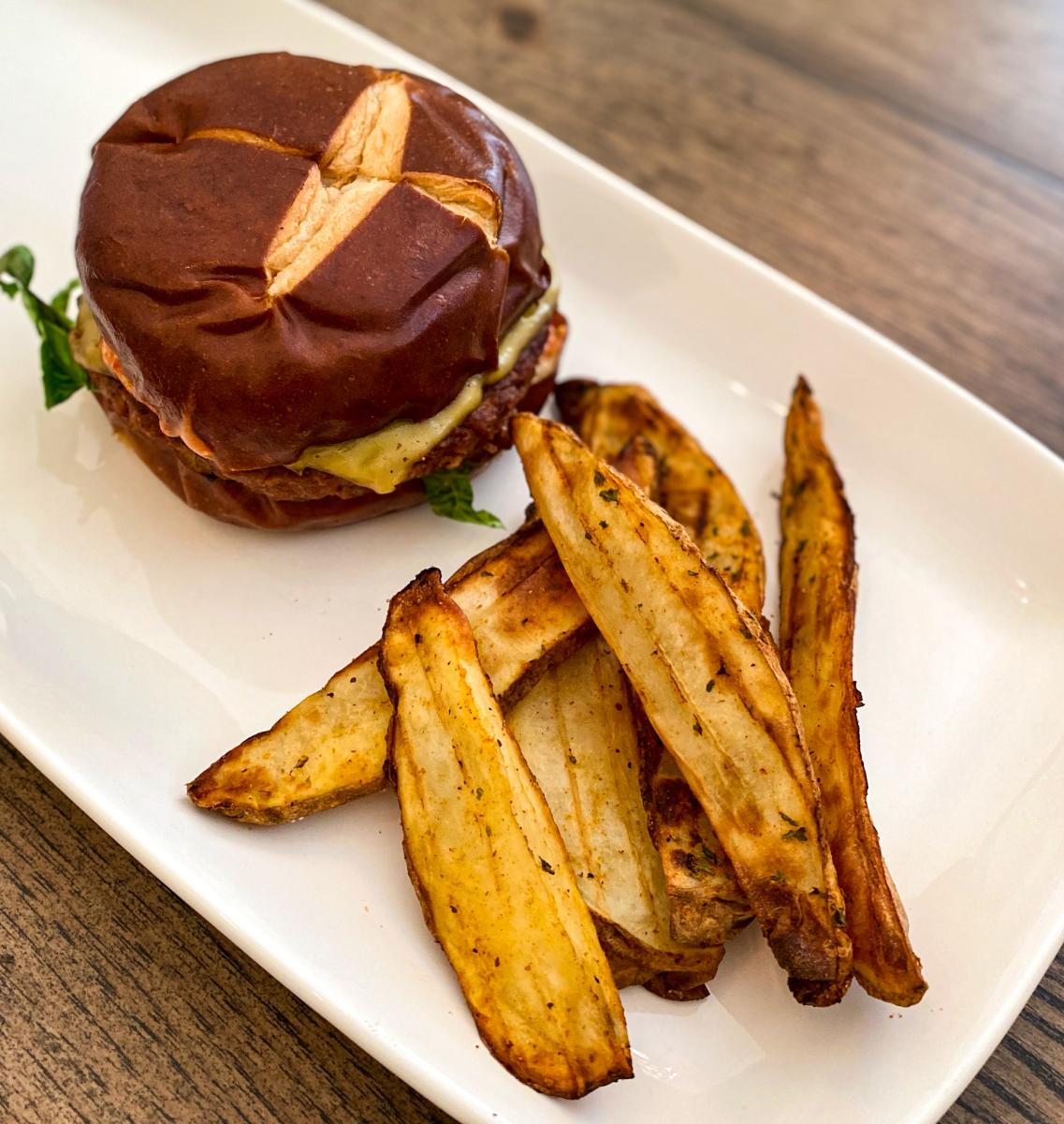 Plated vegetarian burger and potato wedges from Taste and See.