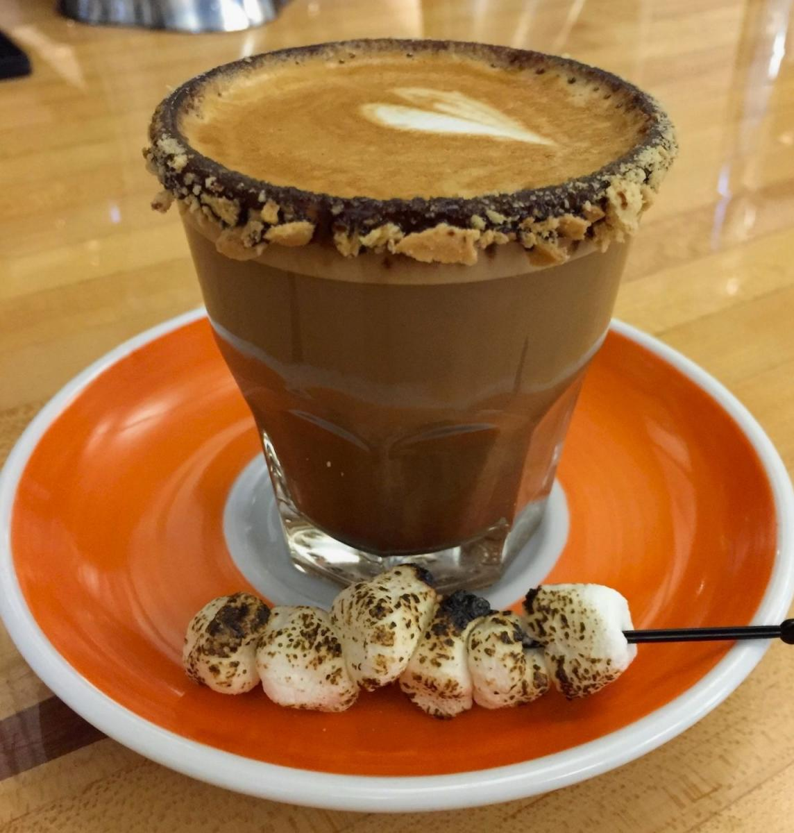 Smortado coffee from Roosevelt Coffee pictured on saucer with toasted marshmallow garnish and gram cracker-crusted rim
