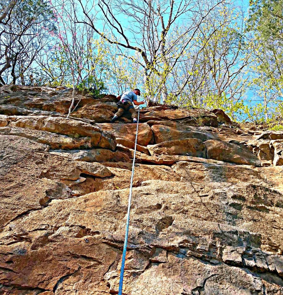 climber atop a rocky bluff
