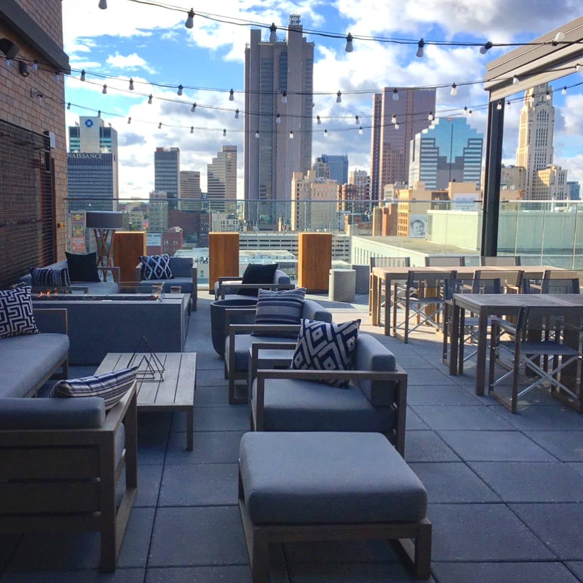 City skyline views and chic patio furniture on stylish rooftop bar at Goodale Station at Canopy by Hilton