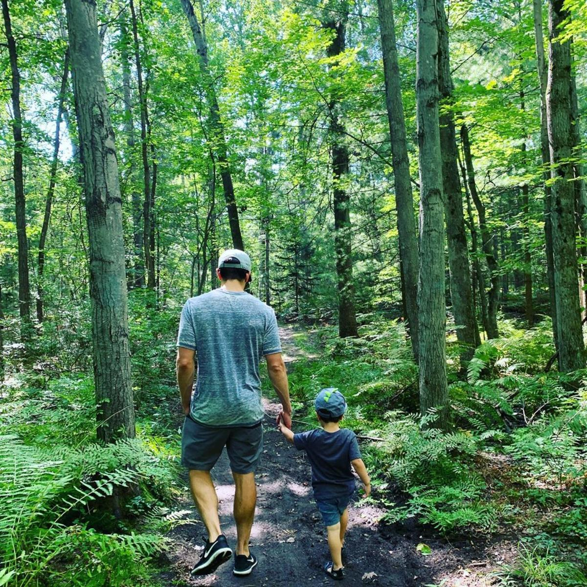 Man and his son walking on a tree-lined path through Midland City Forest