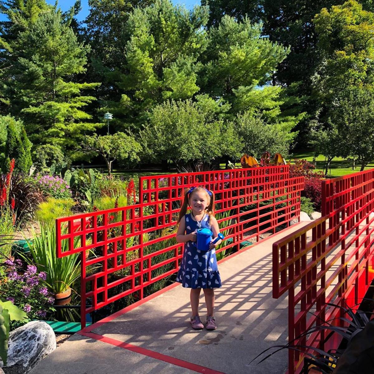 Little girl posing with a watering can at Dow Gardens in Midland