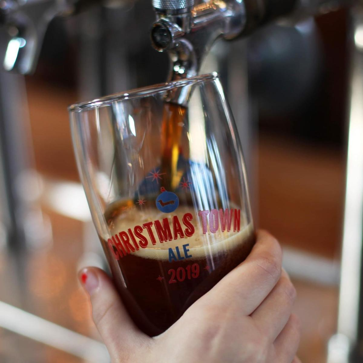 Beer pouring from tap into a Christmas Town Ale collector's glass at Frankenmuth Brewery