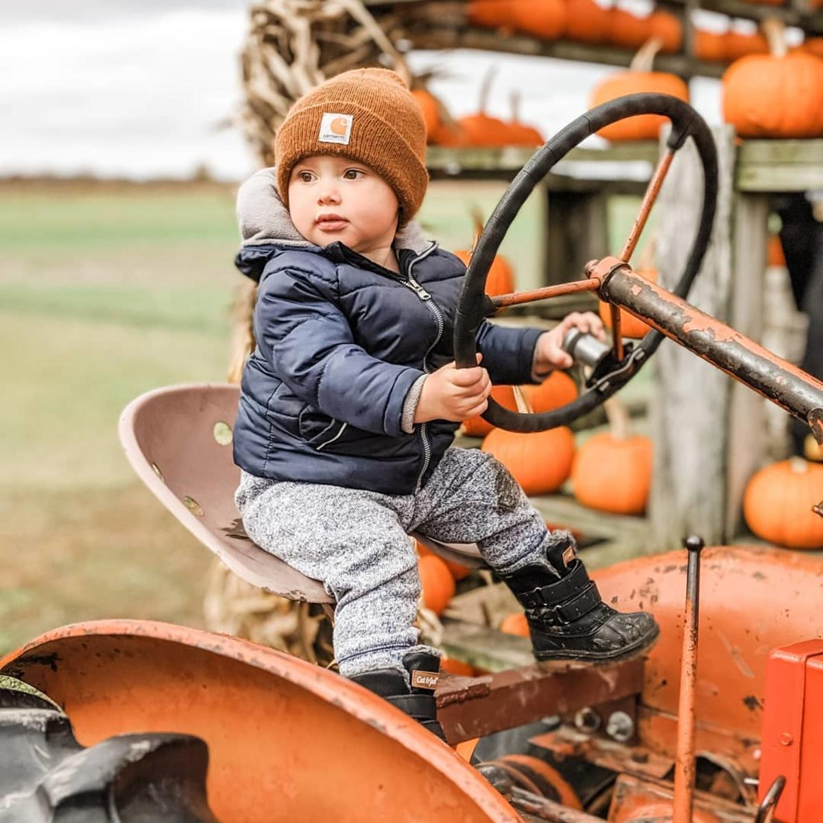 Little boy sitting on an antique tractor at Johnson's Giant Pumpkins in the fall