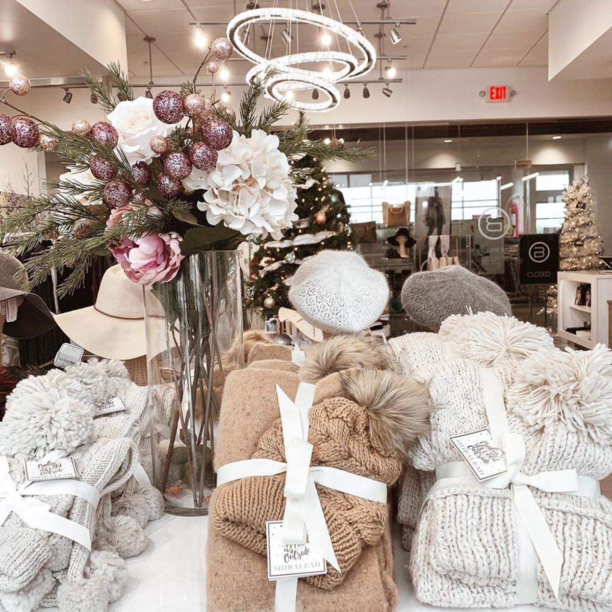 Holiday gift sets of plush hats, scarves, and mittens inside OMONI Boutique in Uptown Bay City