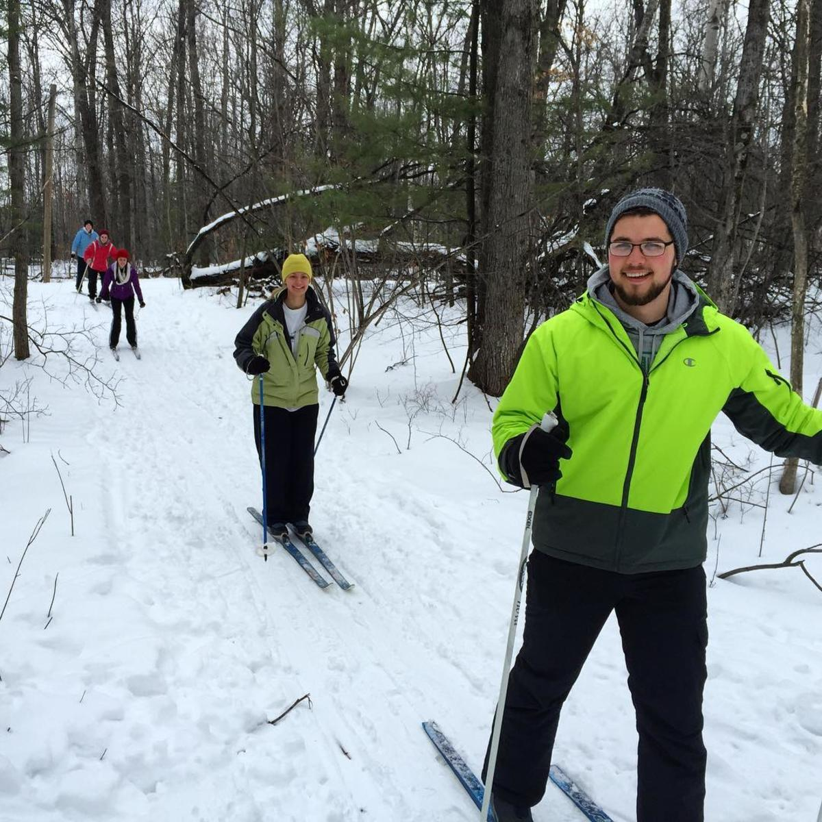 People cross-country skiing & smiling on the trails at Midland City Forest Winter Sports Park