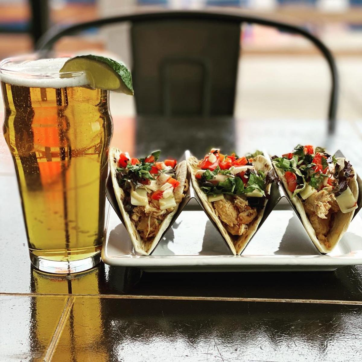 Chef's taco features beautifully presented next to a draft beer garnished with lime at Tavern 101 in Bay City
