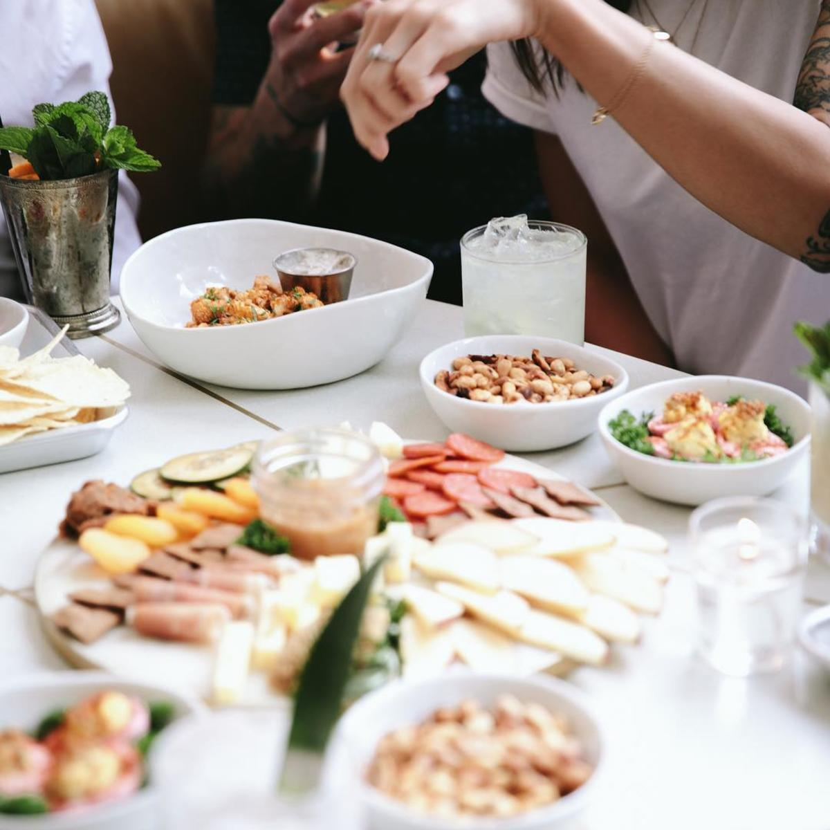 People sharing a charcuterie board and appetizers at The Public House in Bay City