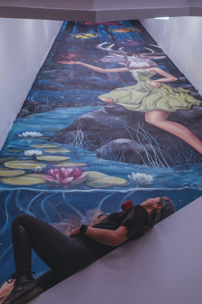 Mandi Caskey viewing her 90ft mural inside Gravity