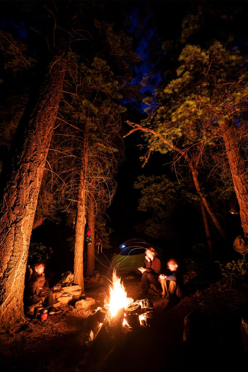 A family enjoys their campfire after a day of backpacking in the Gila National Forest