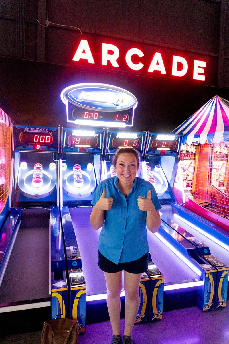 mom with a thumbs up in an neon-lighted arcade