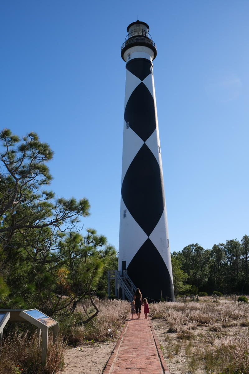 The black-and-white exterior of the Cape Lookout Lighthouse shines bright in the coastal sun.