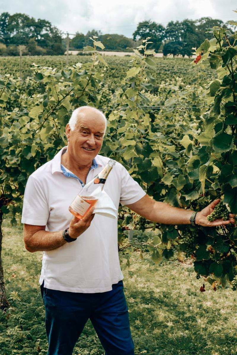 Andrew holding a bottle of wine at English Oak Vineyard