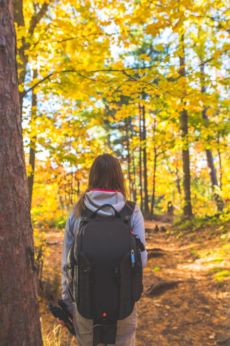 A woman hiking among the fall foliage in Big Bay, MI