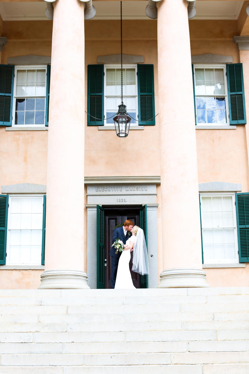 Bride and Groom Kissing at the top of the stairs of Georgia's Old Governor's Mansion in Milledgeville, GA