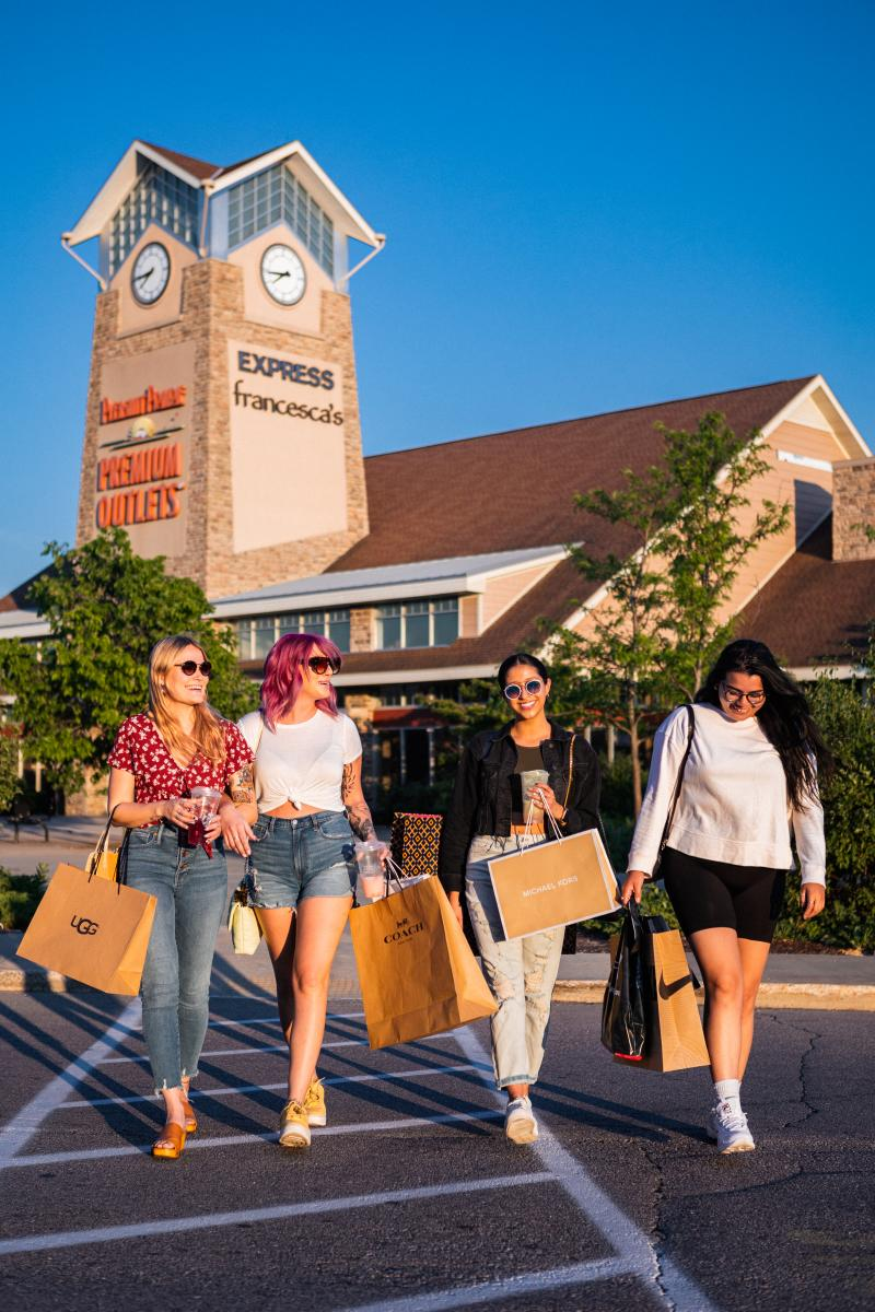 Four Women Shopping at Pleasant Prairie Premium Outlets with Clock Tower in Background