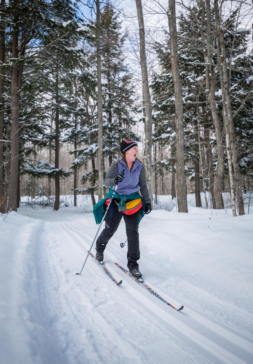 A woman smiling while cross country skiing in Big Bay, MI