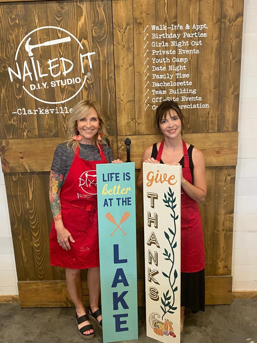 two ladies with painted signs