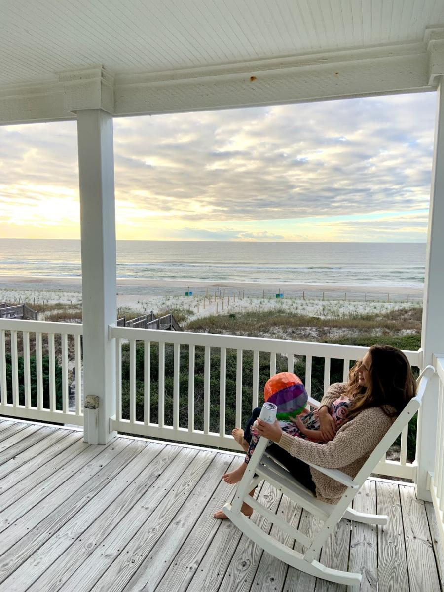 A mother and child relax in the presence of beachfront views from the porch of their rental home.