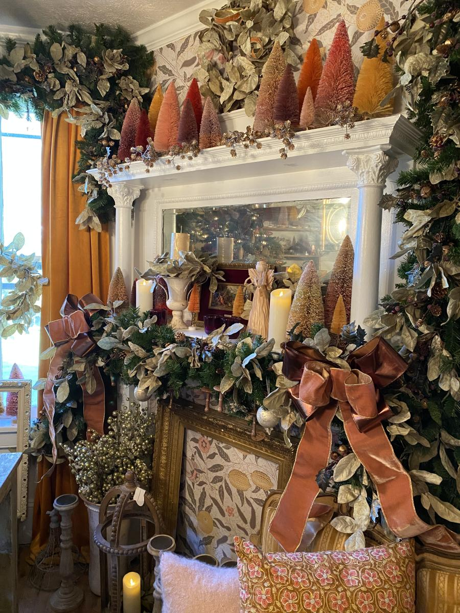 A white fireplace mantle is decorated with small colorful Christmas trees and green and white garland for sale during the Lucketts Holiday Market