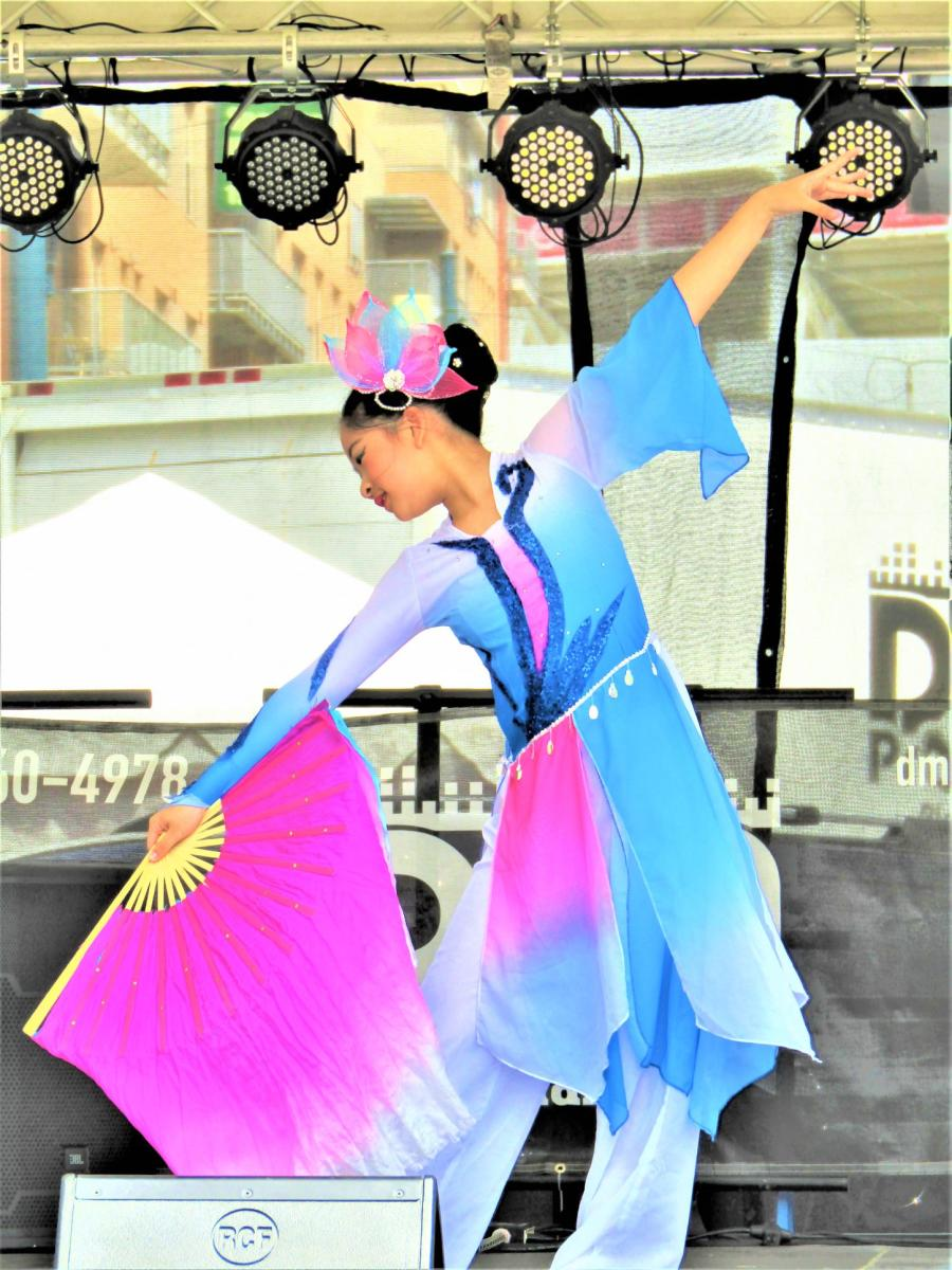 Young woman performing traditional Asian dance in a blue and pink outfit, using a large pink fan