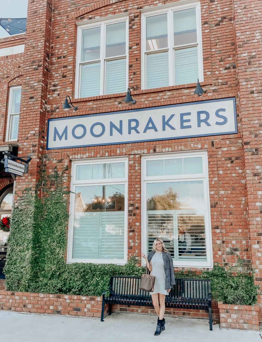The Coastal Blonde poses in front of the Moonrakers front entrance in Beaufort, NC.